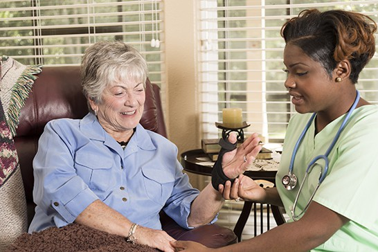 Caring home healthcare nurse conducts medical exam with senior adult woman at her home or nursing home. The female patient recently had wrist surgery and wears a brace. Backyard can be seen through the windows.